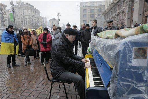Un activista toca el piano para los partidarios de la Unión Europea en una avenida de Kiev, Ucrania, el lunes 16 de diciembre del 2013. En momentos en que están estancadas las conversaciones para reanudar el crédito del Fondo Monetario Internacional, el presidente Viktor Yanukovych viaja el martes 17 a Moscú para ver qué puede ofrecer Rusia a cambio de congelar un acuerdo comercial estratégico con la Unión Europea. (AP Foto/Efrem Lukatsky)