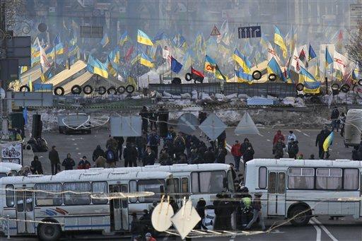Autobuses de la policía bloquean el acceso a una avenida para evitar el enfrentamiento entre activistas a favor de la Unión Europea que se reúnen en la Plaza de la Independencia y seguidores del presidente Viktor Yanukovych, en Kiev, Ucrania, el sábado 14 de diciembre de 2013. (Foto AP/Dmitry Lovetsky)