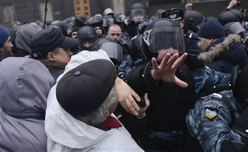Manifestantes chocan con la policía antimotines frente al edificio del gabinete de Ucrania el lunes, 25 de noviembre del 2013, en la continuación de las protestas por la decisión del gobierno de desdeñar la integración con la Unión Europea y fortalecer lazos con Rusia. (Foto AP/Andrew Kravchenko)