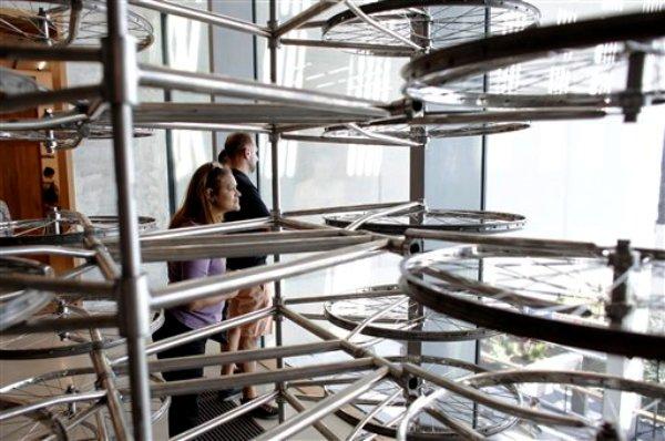 """Visitantes observan la obra """"Stacked"""", un laberinto hecho con ruedas de bicicletas por el artista chino Ai Wei,"""
