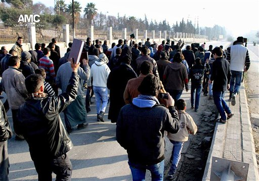 Una imagen de periodistas ciudadanos cedida por el Centro de Medios de Alepo, cuya autenticidad ha sido verificada en base a su contenido y otras labores noticiosas de la AP, muestra a sirios que sostienen el Corán durante una manifestación para detener los combates entre el Estado Islámico en Irak y el Levante y otros rebeldes en Alepo, Siria, el lunes 6 de enero de 2014. (Foto AP/Centro de Medios de Alepo AMC)