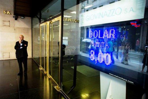 Un hombre se para cerca del cartel luminoso de una casa de cambio en Buenos Aires, Argentina, el jueves 23 de enero de 2014. El peso argentino se desplomó más de un 17% en dos días frente al dólar en el mercado oficial de divisas.(AP foto/Victor R. Caivano)