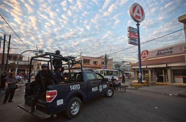 Policías federales llegan hasta el lugar donde incendiaron una farmacia  en Apatzingán, en el estado de Michoacán, México, el miércoles 15 de enero de 2014. (AP Foto/Eduardo Verdugo)