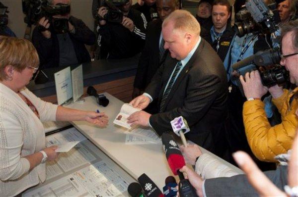 El alcalde de Toronto Rob Ford muestra su pasaporte a una funcionaria para registrarse como candidato a la alcaldía de la ciudad el jueves 2 de enero de 2014. Las elecciones se realizarán en octubre de este año. (Foto AP/The Canadian Press, Victor Biro)