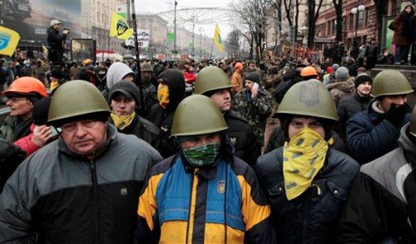 Activistas proeuropeos al frente de una barricada en su campamento de protesta en el centro de Kiev, Ucrania, el sábado 18 de junio de 2014. (Foto AP/Serguei Chuzavkov)