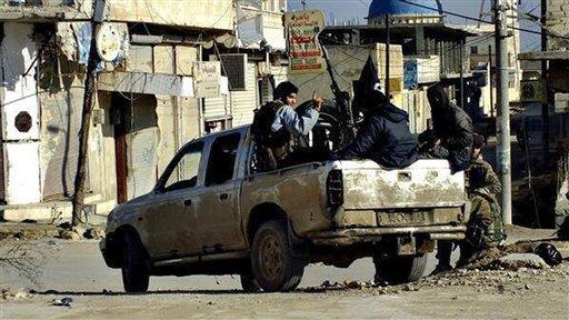 Combatientes del Estado Islámico de Irak y el Levante, grupo vinculado con al-Qaida, se desplazan en un vehículo en Raqqa, Siria, el martes 14 de enero de 2014. Este grupo es combatido por otros grupos rebeldes que pretenden derrocar al presidente Bashar Assad. (AP Foto/militant website)