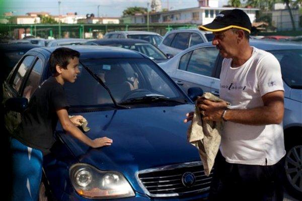 Cubanos limpian un auto chino usado marca Geely para la venta en La Habana, Cuba, el jueves 2 de enero de 2014. En la isla comenzó la venta de automotores gracias a un decreto del presidente Raúl Castro que liberó la oferta minorista de vehículos. (AP Photo/Ramon Espinosa)
