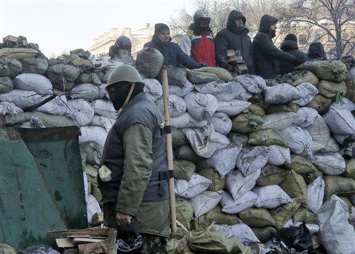 Manifestantes vigilan una barricada frente a un policía antidisturbios en Kiev, Ucrania, el lunes 27 de enero de 2014. Las autoridades ucranianas han descartado imponer el estado de emergencia para controlar la imparable ola de protestas antigubernamentales en el país. (AP foto/Darko Vojinovic)