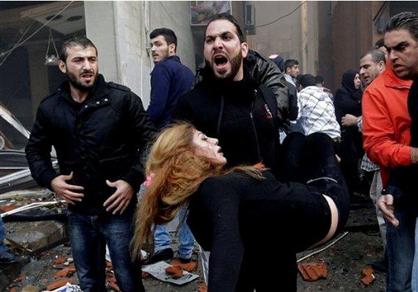 Un libanés carga a una mujer herida para alejarla del lugar donde estalló un automóvil en un área chií y bastión del grupo extremista Jezbolá, en un suburbio del sur de Beirut, el jueves 2 de enero de 2014. (Foto AP/Hussein Malla)