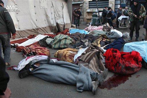 En esta foto del domingo, 15 de diciembre del 2013 proveída por el Aleppo Media Center AMC y cuyo autenticidad ha sido verificada sobre la base de su contenido y otros reportes de la AP, sirios están parados junto a los cadáveres de personas muertas durante un bombardeo aéreo del gobierno contra un barrio rebelde en la ciudad de Alepo.  (Foto AP/Aleppo Media Center, AMC)