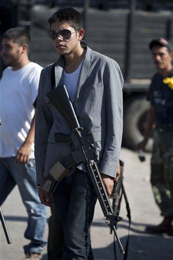Un hombre armado que integra las autodefensas de Michoacán controla la entrada a Antúnez, México, el martes 14 de enero de 2014. El gobierno de México comenzó un nuevo intento por sofocar la violencia generada por enfrentamientos entre grupos de autodefensas y un cartel de drogas en el estado de Michoacán, pero el plan se vio manchado el martes tras una confrontación entre soldados y civiles que según testigos estaban desarmados. (AP foto/Eduardo Verdugo)