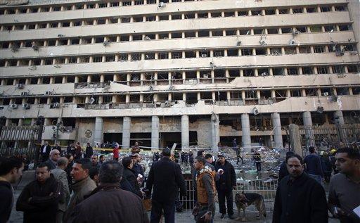 Policías egipcios vigilan tras la explosión en la delegación principal de policía de Egipto en el centro de El Cairo, el viernes 24 de enero de 2014. Un coche bomba estalló en el lugar, matando a varias personas en una oleada de ataques en diferentes puntos de la capital del país. (Foto AP/Khalil Hamra)