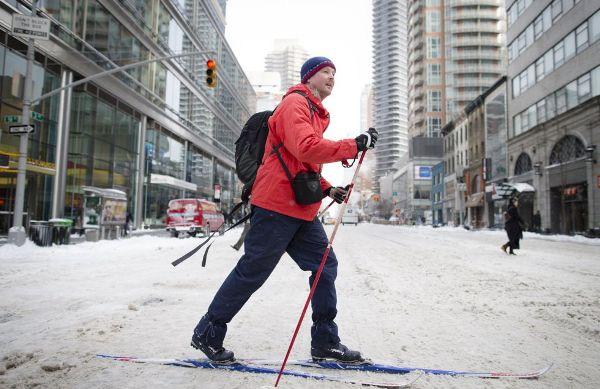 En la imagen, un peatón utiliza sus esquís en la calle 58 en Nueva York. JOHN MINCHILLO (AP)