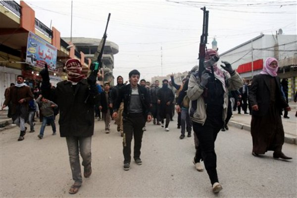Dolientes y milicianos suníes corean lemas el sábado, 4 de enero del 2014, contra el gobierno de Irak durante el funeral de un hombre muerto cuando estallaron choques entre pistoleros de al-Qaida y el ejército iraquí el viernes en Faluya, 65 kilómetros (40 millas) al oeste de Bagdad. (Foto AP)