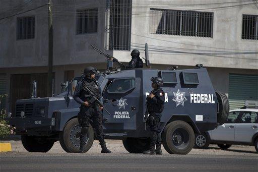 La policía federal patrulla la entrada de Apatzingán, México, el martes 14 de enero de 2014. Soldados y policías federales mantenían una tensa confrontación con autodefensas el martes después que una nueva campaña del gobierno por detener la violencia en el occidental estado de Michoacán cobró varias vidas. (Foto AP/Eduardo Verdugo)