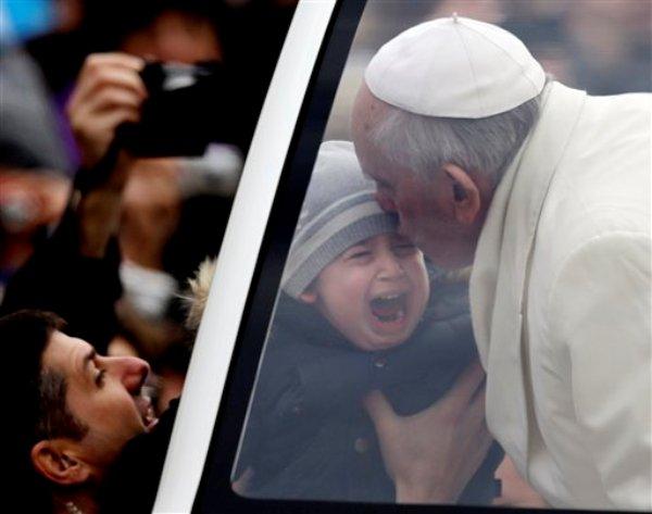El papa Francisco besa a un niño que llora, durante su paseo por la Plaza de San Pedro como parte de su audiencia general semanal en el Vaticano, el miércoles 29 de enero de 2014. (Foto AP/Gregorio Borgia)