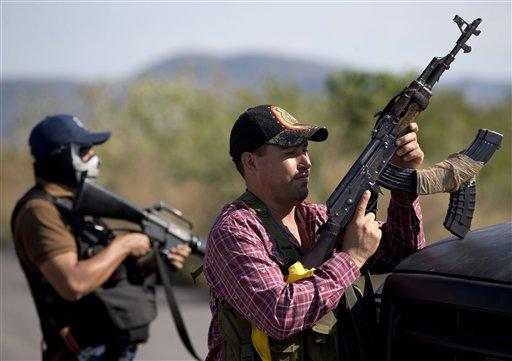 Hombres armados que integran las autodefensas de Michoacán controlan la entrada a Antúnez, México, el martes 14 de enero de 2014. El gobierno de México comenzó un nuevo intento por sofocar la violencia generada por enfrentamientos entre grupos de autodefensas y un cartel de drogas en el estado de Michoacán, pero el plan se vio manchado el martes tras una confrontación entre soldados y civiles que según testigos estaban desarmados. (AP foto/Eduardo Verdugo)