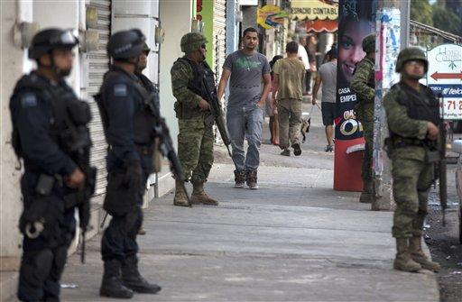 Policías y soldados federales montan guardia en Apatzingán, México, el miércoles 15 de enero de 2014. (AP Foto/Eduardo Verdugo)