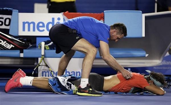 El español Rafael Nadal recibe atención médica por dolores en la espalda durante el juego ante el suizo Stanislas Wawrinka en la final de la rama masculina del Abierto de Australia en Melbourne, Australia, el domingo 26 de enero de 2014. (Foto AP/Rick Rycroft)