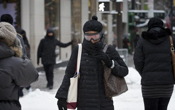 Una peatona usa lentes para esquí al cruzar la Quinta Avenida en Nueva York el viernes 3 de enero de 2014. (Foto AP/John Minchillo)