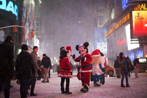 Mickey y Minnie Mouse, dos 'papanoeles' muy especiales, hablan bajo la nieve en Times Square, Nueva York. JOHN MINCHILLO (AP)