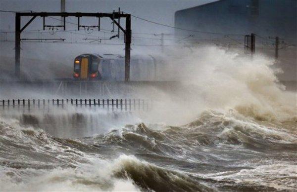 Un tren pasa por la costa de Saltcoats en Escocia el viernes 3 de enero del 2014. Una tormenta invernal cargada de fuertes vientos, marea alta y oleaje azotaron el viernes la costa occidental de Gran Bretaña, provocando inundaciones en los pueblos y área de tierras bajas. Gales, el suroeste de Inglaterra y el norte de Irlanda son las zonas más afectadas por la tormenta, la más reciente en una serie condiciones invernales extremas.(Foto AP/PA, Danny Lawson)