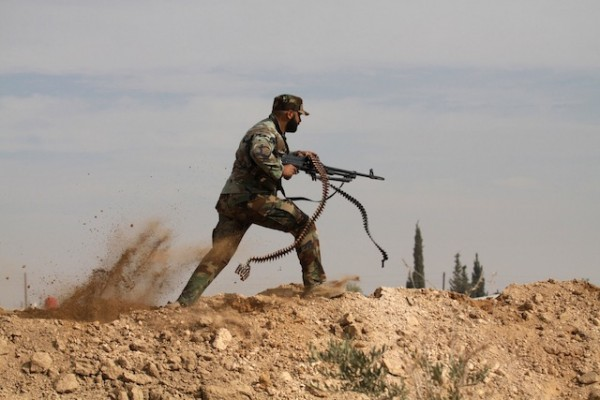 Un combatiente chiíta en una foto de archivo del 22 de noviembre del 2013 se enfrenta a los rebeldes del Ejército Libre Sirio en el pueblo de Hata en el área rural de Damasco, la capital siria. Por lo menos 22 personas entre ellas a 14 niños, en Alepo, la disputada ciudad del norte de Siria, donde aviones del gobierno sirio arrojaron barriles bomba, dijeron activistas de oposición el domingo 15 de diciembre del 2013. (Foto AP/Jaber al-Helo)