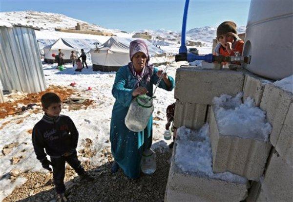 Una refugiada siria se aprovisiona de agua en un campamento de refugiados en Arsal, Líbano, el domingo, 15 de diciembre del 2013. La ONU dijo el lunes que va a necesitar 13.000 millones de dólares en ayuda en el 2014 para al menos 52 millones de personas en 17 países, incluyendo los millones de sirios que han sido desplazados por la guerra civil. (Foto AP/Bilal Hussein)