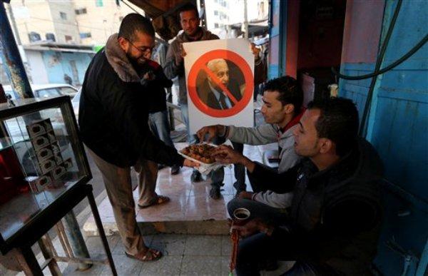 Un palestino ofrece bocadillos a gente en una calle después de enterarse de la muerte del ex primer ministro israelí Ariel Sharon, en Khan Younis, al sur de la Franja de Gaza, el sábado 11 de enero de 2014. (Foto AP/Hatem Moussa)
