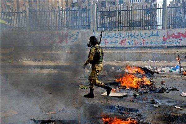 Un soldado camina entre el humo tras los enfrentamientos de los simpatizantes del derrocado presidente Mohamed Morsi y las autoridades en Alejandría, Egipto, el viernes 3 de enero de 2014. Los enfrentamientos se extendieron a zonas residenciales densamente pobladas en varias ciudades y provincias, incluidas El Cairo, Giza, Ismailia y Alejandría. (Foto AP/Heba Khamis)