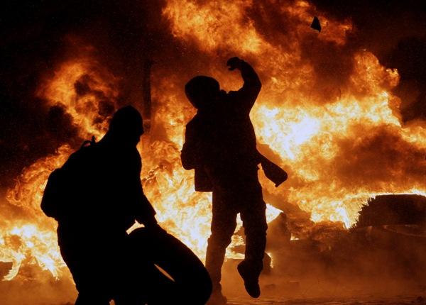 Un manifestante lanza una piedra durante enfrentamientos con la policía en el centro de Kiev, Ucrania, el miércoles 22 de enero de 2014.   (AP Foto/Darko Vojinovic)
