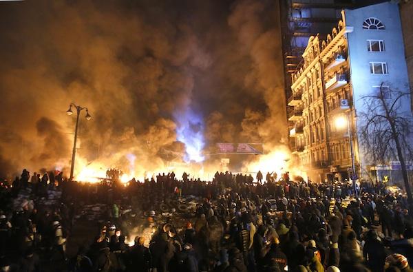 Llamas y humo negro salen de barricadas de neumáticos incendiados durante un enfrentamiento entre manifestantes y policías en el centro de Kiev, Ucrania, el sábado 25 de enero de 2014. (AP Foto/Sergei Grits)