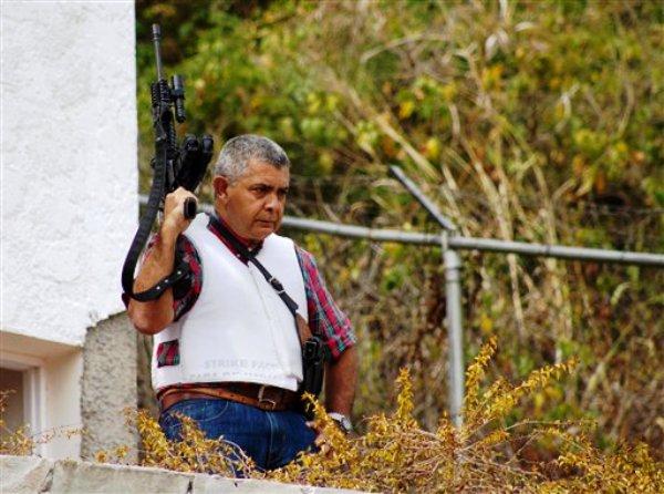 El general venezolano retirado Angel Vivas, vigila armado su propiedad en Caracas, Venezuela, el domingo 23 de febrero de 2014. El presidente Nicolás Maduro ordenó el sábado el arresto e investigación del general por sus declaraciones vertidas en YouTube y Twitter. Maduro dijo que Vivas está instigando a la violencia. (Foto AP/Juan Manuel Hernández)