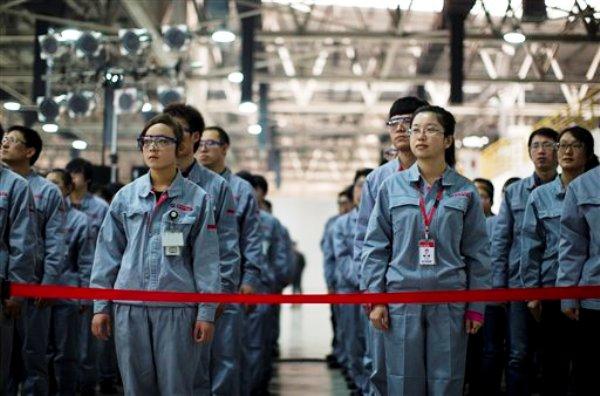 Empleados de Foton Cummins Engine observan al secretario de Estado John Kerry recorre la planta en Beijing, China, el sábado 15 de febrero de 2014. El funcionario estadounidense habló sobre cambio climático y la cooperación entre China y EEUU. (Foto AP/Evan Vucci, Pool)