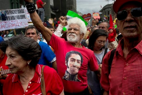 Un hombre vestido con una camiseta con la imagen del héroe independentista de Venezuela Simón Bolivar entona cánticos oficialistas durante una marcha organizada por el gobierno en Caracas, Venezuela, el domingo 23 de febrero de 2014. (Foto AP/Rodrigo Abd)