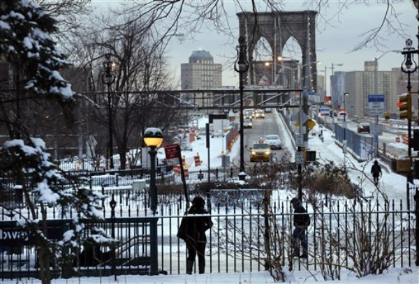 Peatones recorren aceras cubiertas de nieve y el tráfico cruza el puente de Brooklyn, miércoles 22 de enero de 2014 en Nueva York. Una tormenta invernal con nieve y mucho frío azota el noreste de Estados Unidos.(AP Foto/Mark Lennihan)