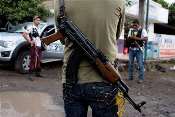 En esta fotografía del 16 de enero de 2014, hombres armados pertenecientes al Consejo de Autodefensas de Michoacán (CAM) montan guardia en un retén instalado a la entrada de Antúnez, México. El gobierno anunció el lunes 27 de enero de 2014 que había logrado un acuerdo con los líderes del grupo para incorporar a los civiles armados a las unidades denominadas Cuerpos de Defensa Rurales. (Foto AP/Eduardo Verdugo/Archivo)