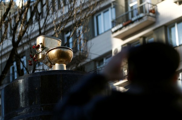 A man takes a picture of the toilet bowl on the pedestal of a statue of Soviet state founder Vladimir Lenin, which was toppled by protesters last December, in Kiev February 3, 2014. Ukrainian President Viktor Yanukovich returned to his desk on Monday after four days of sick leave, while the political opposition pressed for further concessions to end more than two months of street protests. REUTERS/David Mdzinarishvili (UKRAINE - Tags: POLITICS CIVIL UNREST)