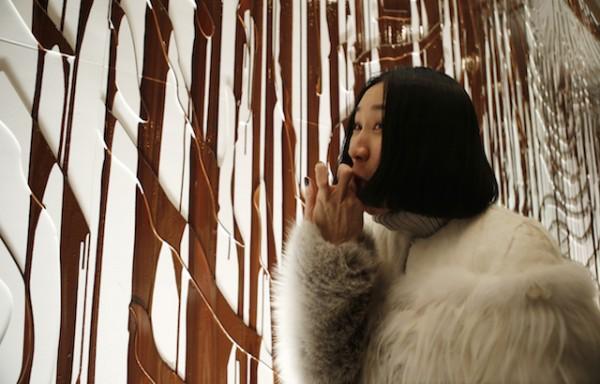 La editora en jefe de la revista Lucky, Eva Chen, prueba el chocolate líquido que chorrea por una pared durante la presentación de la colección otoño-invierno de Opening Ceremony en la Semana de la Moda de Nueva York, el domingo 9 de febrero del 2014. (AP Foto/Kathy Willens)