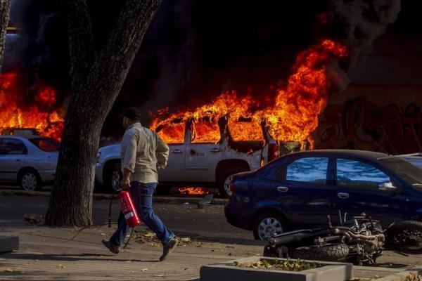 Foto: una persona camina con un extintor cerca a un vehículo incendiado hoy, miércoles 12 de febrero de 2014, durante una marcha convocada por la oposición, en Caracas (Venezuela). EFE/Miguel Gutiérrez