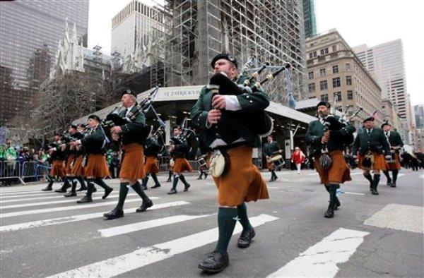 Los gaiteros del County Tyrone Pipe Band participan en el desfile por el Día de San Patricio en la Quinta Avenida el lunes 17 de marzo del 2014 en Nueva York. En el centro se ve a la Catedral de San Patricio donde se realizan trabajos de reparación. El desfile en que estuvo ausente el alcade de Nueva York, Bill de Blasio, se desarrolló en medio de tensiones por la exclusión de los gays. (Foto AP/Mark Lennihan)