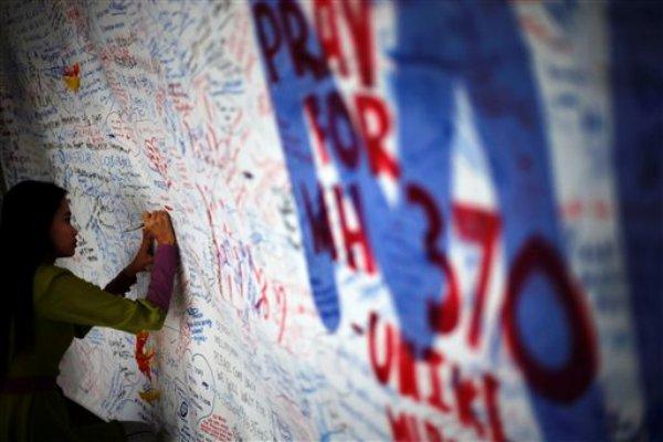 Una mujer escribe un mensaje dedicado a las 239 personas que iban a bordo del vuelo MH370 de Malaysia Airlines y que desapareció hace una semana, el sábado 15 de marzo de 2014, en Sepang, Malasia. (Foto AP/Wong Maye-E)