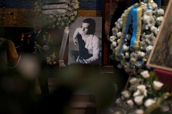 Una foto del virtuoso guitarrista flamenco Paco de Lucía en su juventud se observa cerca de su  féretro en su natal Algeciras, en el sur de España, el 1 de marzo de  2014. De Lucia murió en México el miércoles 26 de febrero a los 66 años. (AP Foto/Laura León)