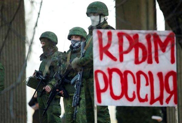 """Un grupo de pistoleros no identificados en uniforme de camuflaje bloquea la entrada al Parlamento de Crimea en Simferopol, Ucrania, el sábado 1 de marzo del 2014. El cartel dice """"Crimea Rusia"""". (AP Foto/Ivan Sekretarev)"""