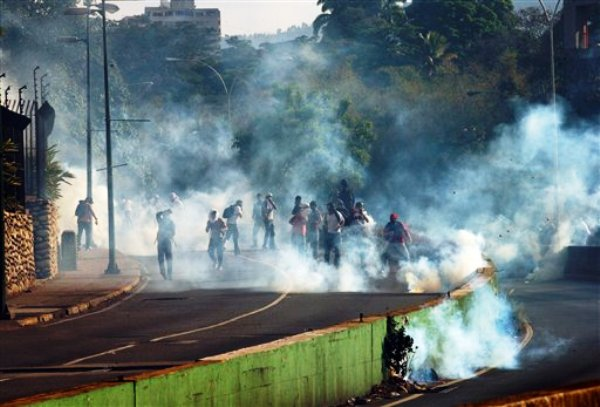 Manifestantes se alejan de nubes de gas lacrimógeno lanzadas por la policía durante una protesta antigubernamental en Caracas, Venezuela, el jueves 20 de marzo de 2014. (Foto AP/Fernando Llano)