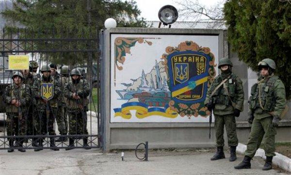 Soldados ucranianos (izquierda) y hombres armados no identificados (derecha) a la entrada de una base de infantería en Perevalne, Ucrania, el domingo 2 de marzo de 2014. Cientos de soldados no identificados llegaron a la base en la región de Crimea en varios camiones y vehículos blindados con placas rusas, que han rodeado la instalación y no permiten a los soldados ucranianos entrar o salir. (Foto AP/Darko Vojinovic)