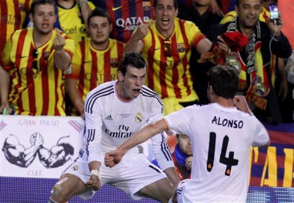 Gareth Bale, del Real Madrid, celebra con Xabi Alonso, luego de anotar el segundo tanto de su equipo en la final de la Copa del Rey ante el Barcelona, el miércoles 16 de abril de 2014 (AP Foto/Alberto Saiz)