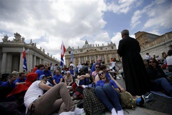 Un grupo de fieles polacos reza frente a la Basílica de San Pedro en el Vaticano el sábado 26 de abril de 2014. Peregrinos y fieles han comenzado a reunirse en Roma para asistir a la ceremonia de canonización de Juan XXIII y de Juan Pablo II que se celebrará el domingo 27 de abril. (Foto AP/Andrew Medichini)
