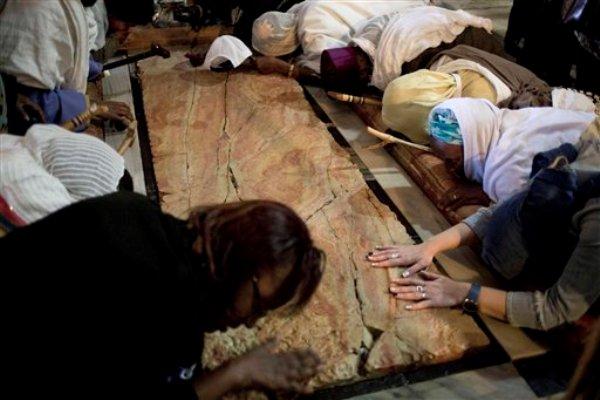 Fieles oran en la Piedra de la Unión, donde según la creencia, Jesús fue colocado después de que lo crucificaran, en el interior de la Iglesia del Santo Sepulcro en Jerusalén, el jueves 17 de abril de 2014. (AP Foto/Ariel Schalit)