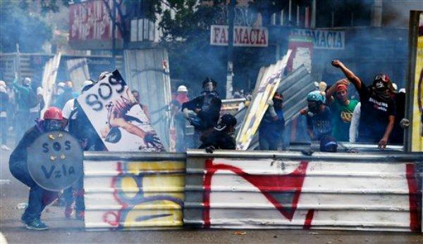 Manifestantes antigubernamentales se protegen de los gases lacrimógeneos lanzados por la Policía Nacional Bolivariana durante enfrentamientos en Caracas, Venezuela, el martes 1 de abril de 2014. Los manifestantes se habían congregado para marchar hacia la Asamblea Nacional con la legisladora de oposición María Corina Machado, quien fue desaforada la semana pasada tras dirigirse a una reunión de la OEA en Washington sobre la situación en Venezuela. La policía antimotines evitó que los manifestantes llegaran a la Asamblea Nacional. (Foto AP/Fernando Llano)